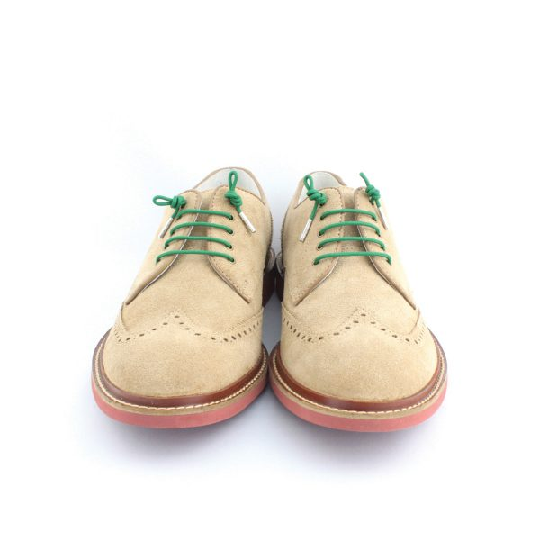 sand coloured shoes with green laces